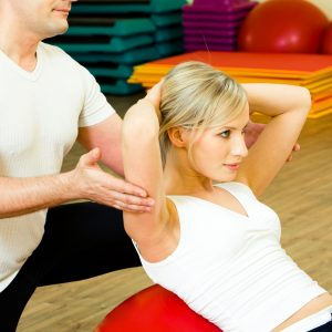 Photo of woman doing physical exercise with man near by